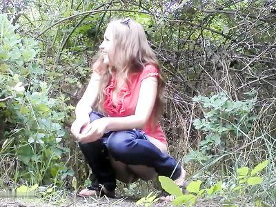 Улыбчивая девушка писает в лесу и общается с поглядывающим через кусты парнем