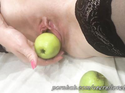 Барышня в черных чулках и с выбритой киской занимает вагинальным фистингом с яблоками