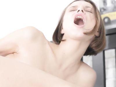 Коротко стриженная брюнетка с маленькой грудью дрочит в кровати и стонет