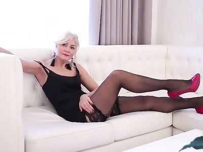 Зрелая сексуальная блондинка в черных чулках приятно дрочит киску